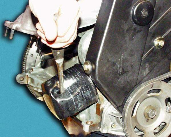 Пробиваем фильтр отверткой(подальше от мотора и перпендикулярно штуцеру) и выкручиваем его, используя отвертку как рычаг